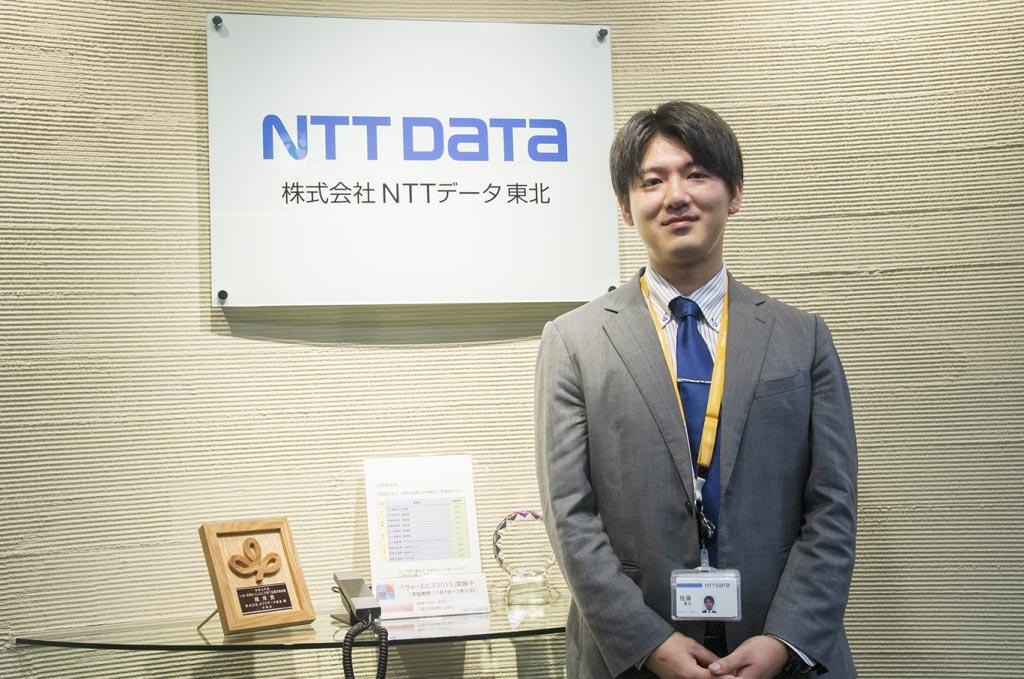 会社入り口でのNTTデータ東北の若手社員の写真